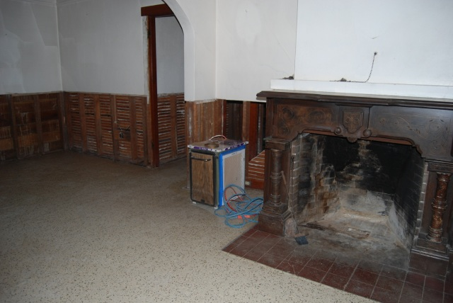 the living room after demo-our fireplace is stone trompe l'oeil painted to look like walnut.